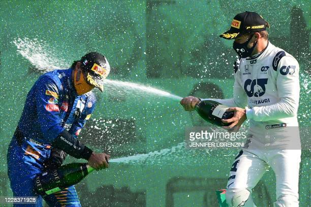 Winner AlphaTauri's French driver Pierre Gasly sprays champagne as he celebrates with second placed McLaren's Spanish driver Carlos Sainz Jr on the...