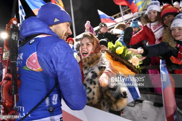 Winner Anton Shipulin of Russia gives his flowers to an eager Russian fan after the men's 10km sprint event at the IBU Biathlon World Cup in...