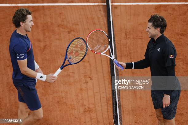Winner Austria's Dominic Thiem congratulates Norway's Casper Ruud as they touch their rackets at the end of their men's singles third round tennis...