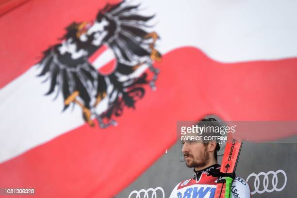 Winner Austria's Marcel Hirscher looks on under an Austrian flag during the podium ceremony of the Men's giant slalom race at the FIS Alpine Skiing...