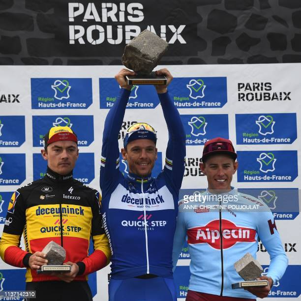 Winner Belgium's Philippe Gilbert celebrates his trophy next to second-placed Germany's Nils Politt and third-placed Belgium's Yves Lampaert on the...