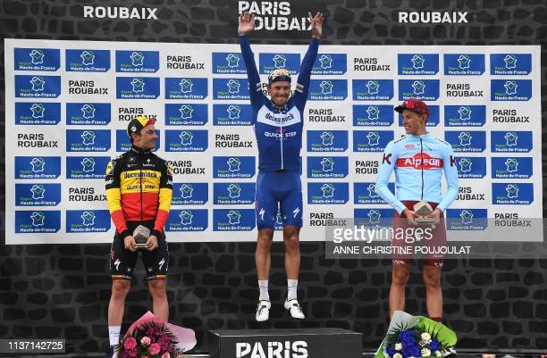 Winner Belgium's Philippe Gilbert celebrates his victory next to second-placed Germany's Nils Politt and third-placed Belgium's Yves Lampaert on the...