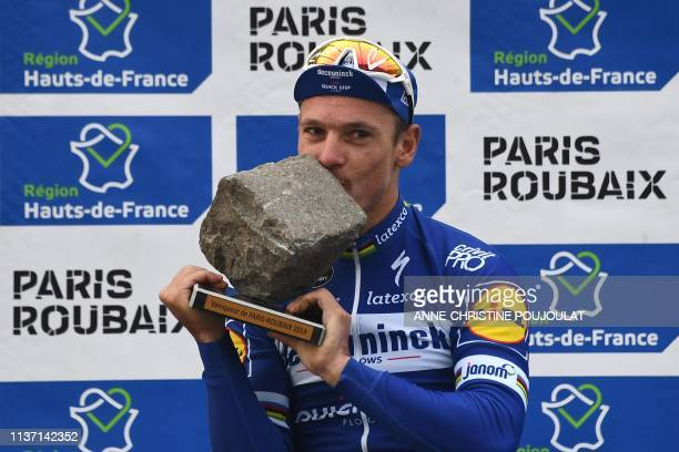 Winner Belgium's Philippe Gilbert kisses his trophy on the podium of the 117th edition of the Paris-Roubaix one-day classic cycling race, between...