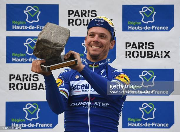 Winner Belgium's Philippe Gilbert raises his trophy on the podium of the 117th edition of the Paris-Roubaix one-day classic cycling race, between...