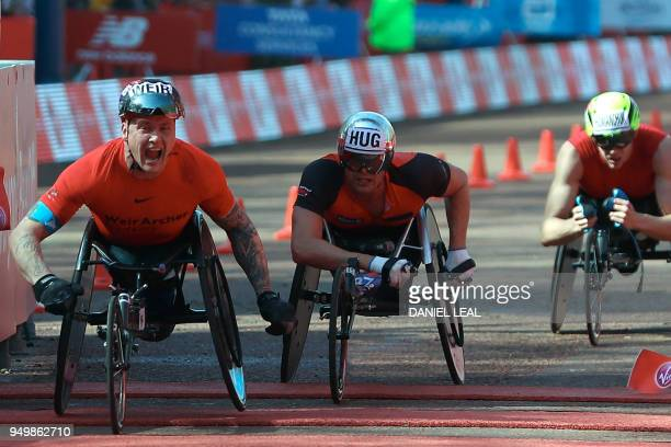 Winner Britain's David Weir secondplaced Switzerland's Marcel Hug and thirdplaced US Daniel Romanchuk cross the finish line of the elite wheelchair...