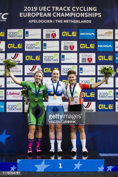 Winner British Emily Nelson in the midst of Irish Shannon McCurley and Portuguese Maria Martins during the honoring of the women's scratch final at...