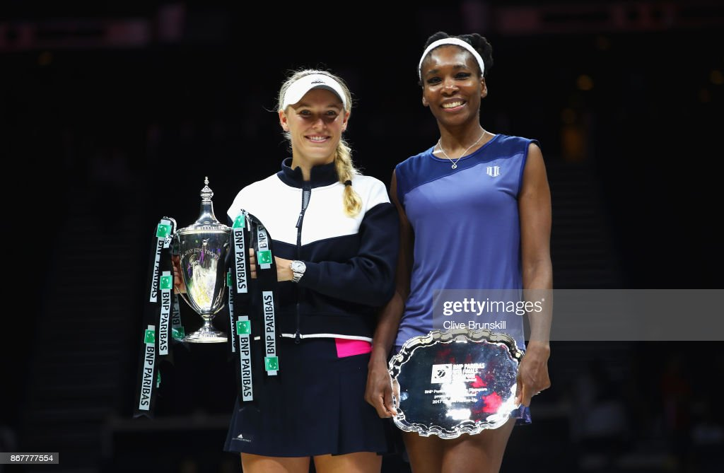 Winner Caroline Wozniacki of Denmark celebrates victory with the Billie Jean King trophy and runner up Venus Williams of the United States after the Singles Final during day 8 of the BNP Paribas WTA Finals Singapore presented by SC Global at Singapore Sports Hub on October 29, 2017 in Singapore.