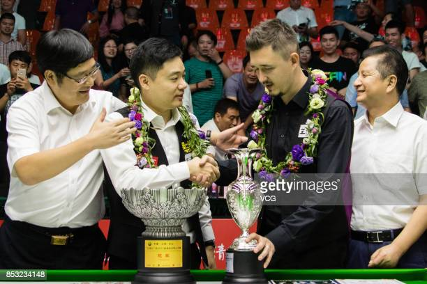 Winner Ding Junhui of China and the runnerup Kyren Wilson of England celebrate with their trophies after the final match on day seven of the World...