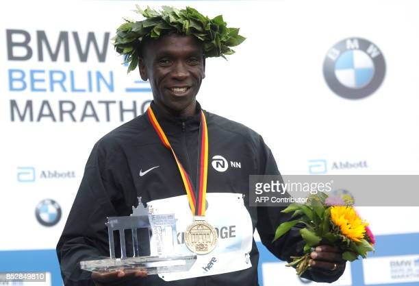 Winner Eliud Kipchoge of Kenya celebrates on the podium after the Berlin Marathon on September 24 2017 in Berlin / AFP PHOTO / MICHELE TANTUSSI