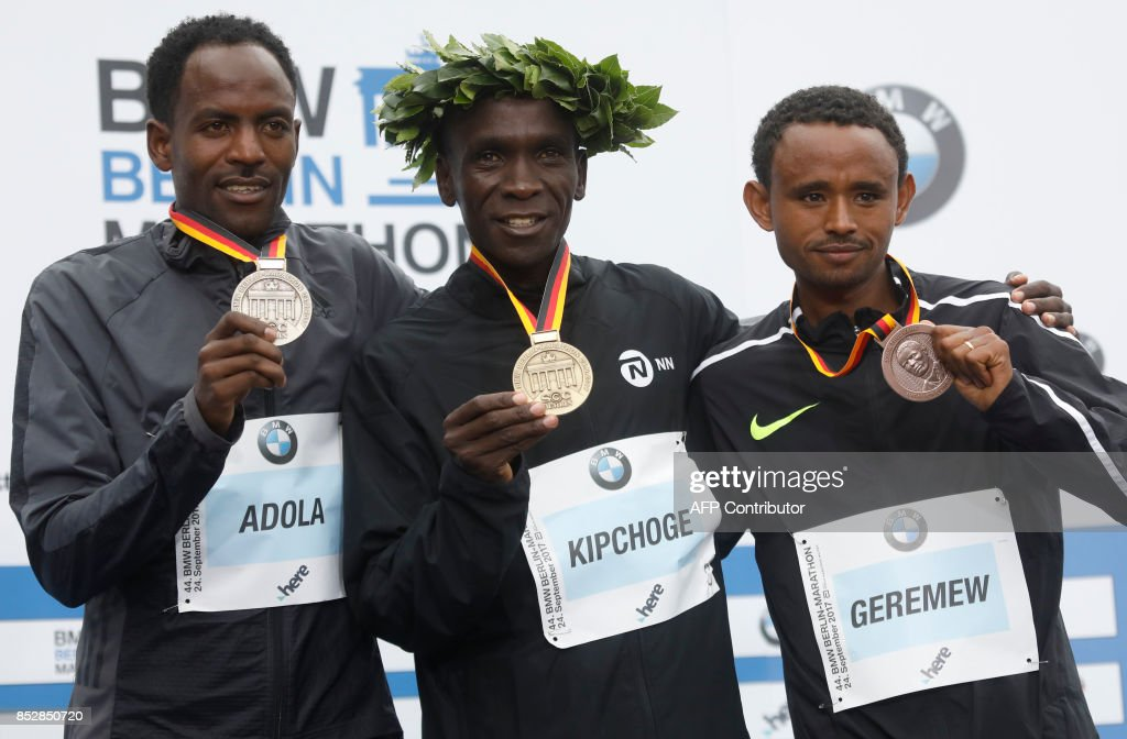 Winner Eliud Kipchoge of Kenya (C), second palced Ethiopian Guye Adola (L) and tird placed Ethiopian Mosinet Geremew celebrate on the podium after the Berlin Marathon on September 24, 2017 in Berlin. /
