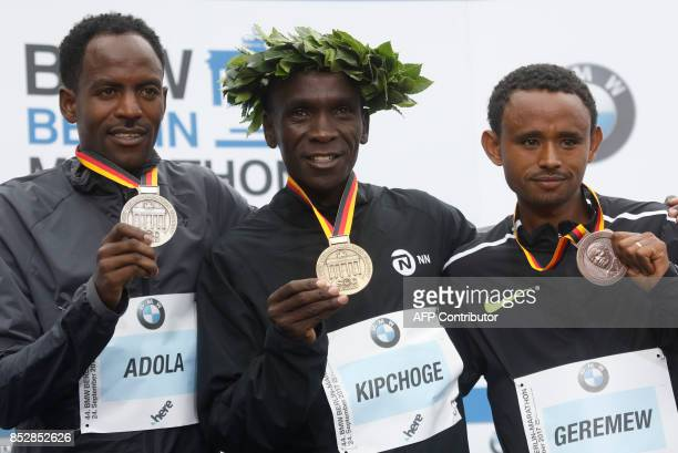 Winner Eliud Kipchoge of Kenya second palced Ethiopian Guye Adola and tird placed Ethiopian Mosinet Geremew celebrate on the podium after the Berlin...