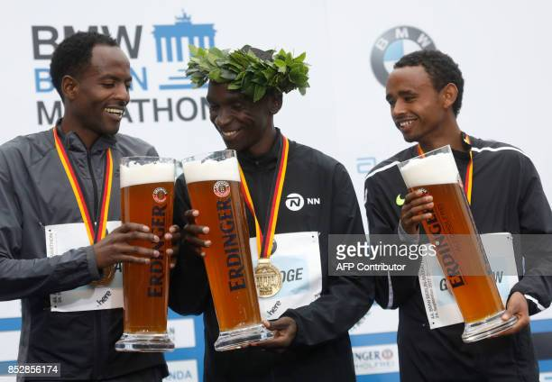 Winner Eliud Kipchoge of Kenya second palced Ethiopian Guye Adola and tird placed Ethiopian Mosinet Geremew celebrate with beer on the podium after...