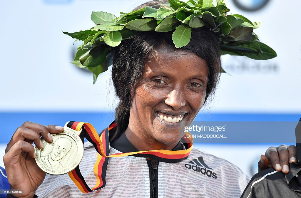 Winner Ethiopian Aberu Kebede poses on the podium with her gold medal after winning the women's run of the 43rd Berlin Marathon in Berlin on September 25, 2016. / AFP / John MACDOUGALL