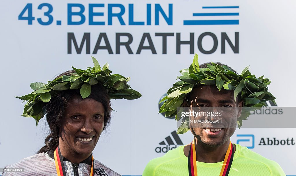 Winner Ethiopian Kenenisa Bekele and winner Ethiopian Aberu Kebede pose on the podium after winning the 43rd Berlin Marathon in Berlin on September 25, 2016. / AFP / John MACDOUGALL