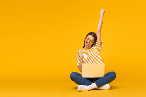 Winner! Excited smiling girl sitting on floor with laptop, raising one hand in the air is she wins, isolated on yellow background 1150254153