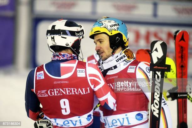 Winner Felix Neureuther of Germany talks to Dave Ryding of Great Britain who failed to finish his second run after the Men's FIS Alpine Ski World Cup...