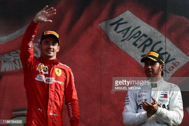 TOPSHOT Winner Ferrari's Monegasque driver Charles Leclerc celebrates next to third placed Mercedes' British driver Lewis Hamilton on the podium...