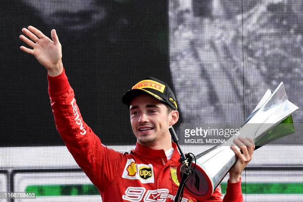 Winner Ferrari's Monegasque driver Charles Leclerc celebrates with his trophy on the podium after the Italian Formula One Grand Prix at the Autodromo...