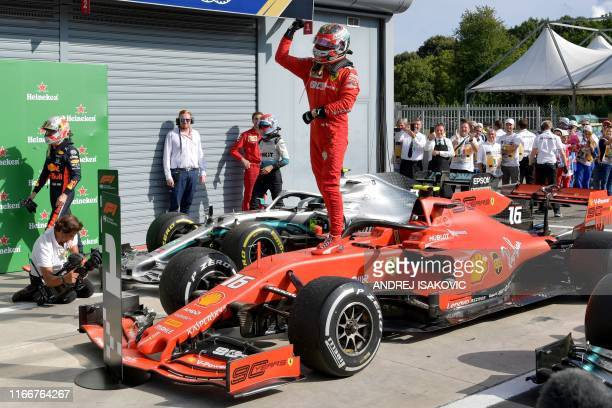 Winner Ferrari's Monegasque driver Charles Leclerc stands on his car to celebrate after the Italian Formula One Grand Prix at the Autodromo Nazionale...