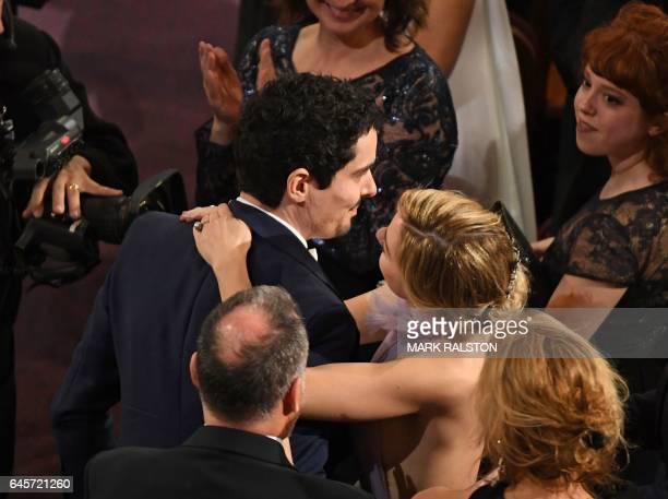 Winner for Best Director 'La La Land' Damien Chazelle is embraced by his partner on stage at the 89th Oscars on February 26 2017 in Hollywood...