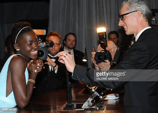 Winner for Best Supporting Actress in 12 Years a Slave Lupita Nyong'o looks at the plaque bearing her name that will be added to her trophy at the...