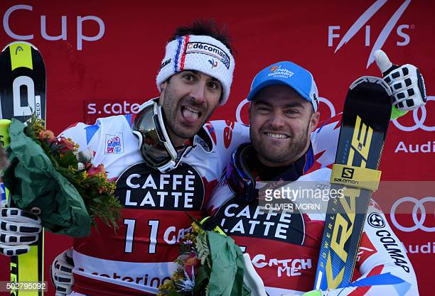 Winner France's Adrien Theaux and thirdplaced France's David Poisson celebrate on the podium of the FIS Alpine World Cup Men's Downhill in Santa...