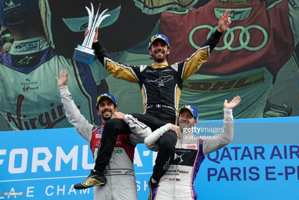 Winner France's Jean-Eric Vergne of the Formula E team Techeetah (C), second placed Brazil's Lucas Di Grassi of the Formula E team ABT Schaeffler Audi Sport (L) and third placed Britain's Sam Bird of the Formula E team DS automobiles Virgin Racing jubilate on the podium after the race during the Formula E championship around The Invalides Monument close to The Eiffel Tower in Paris on April 28, 2018.