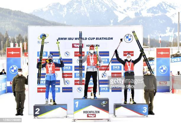 Winner Germany's Arnd Peiffer poses on the podium with second placed Martin Ponsiluoma of Sweden and third placed Tarjei Boe of Norway after the...