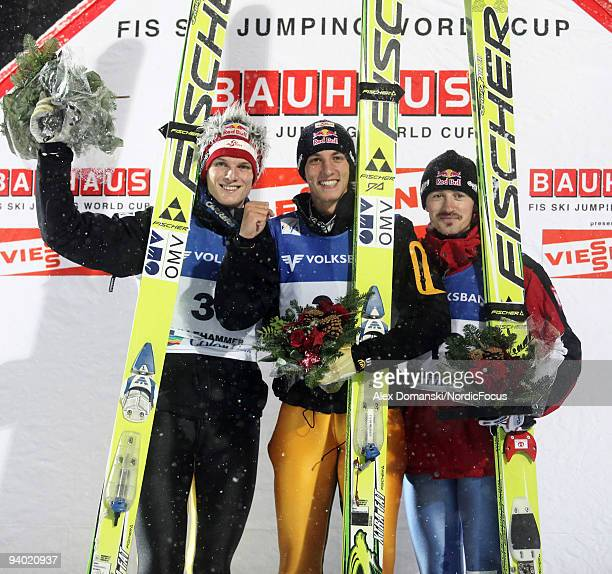 Winner Gregor Schlierenzauer of Austria poses on the Podium together with Thomas Morgenstern of Austria who placed second and Adam Malysz of Poland...