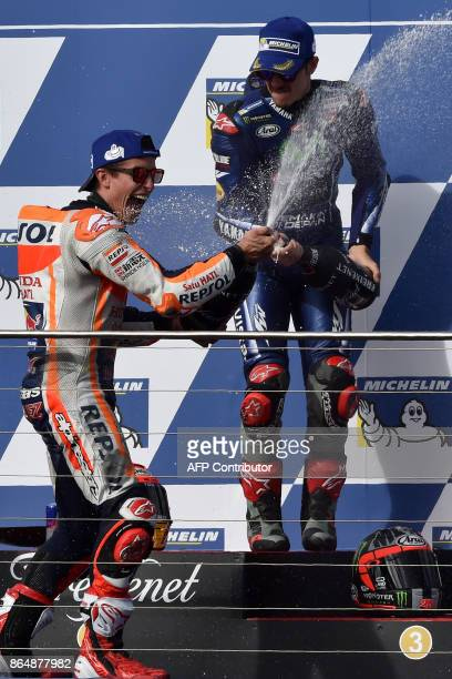 Winner Honda rider Marc Marquez of Spain and thirdplaced Yamaha rider Maverick Vinalesof Spain celebrate with champagne at the end of the Australian...
