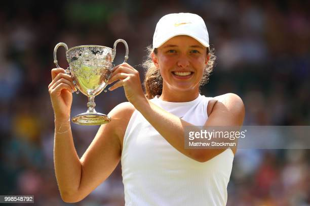 Winner Iga Swiatek of Poland celebrates with the trophy after the Girls' Singles final on day twelve of the Wimbledon Lawn Tennis Championships at...