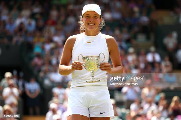 Winner Iga Swiatek of Poland holds her trophy after the Girls' Singles final on day twelve of the Wimbledon Lawn Tennis Championships at All England...