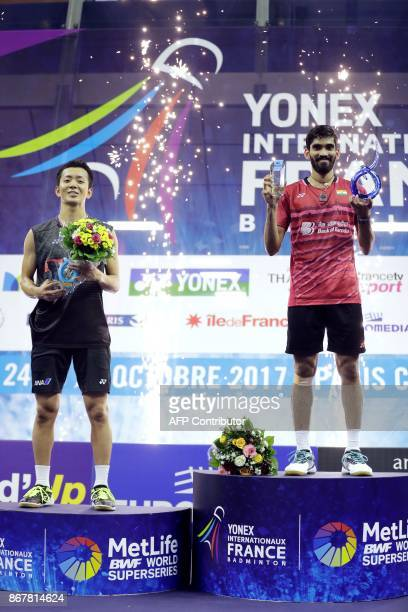 Winner India's Srikanth Kidambi and secondplaced Japan's Kenta Nishimoto pose with their trophies on the podium after the men's singles final at the...