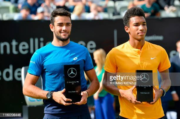 Winner Italy's Matteo Berrettini poses with his trophy next to Canada's Felix AugerAliassime at the end of their final at the ATP Mercedes Cup tennis...