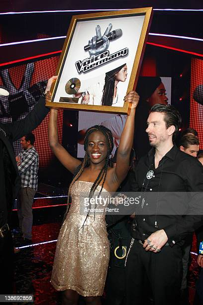 Winner Ivy Quainoo celebrates with Alec 'Boss Burns' Voelkel of the band The BossHoss after the music tv show 'The Voice of Germany' on February 10...
