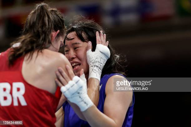 Winner Japan's Sena Irie and Britain's Karriss Artingstall hug after their women's feather semi-final boxing match during the Tokyo 2020 Olympic...
