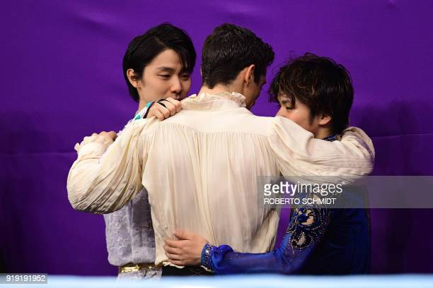 Winner Japan's Yuzuru Hanyu talks with third-placed Spain's Javier Fernandez and second-placed Japan's Shoma Uno during the venue ceremony after the...