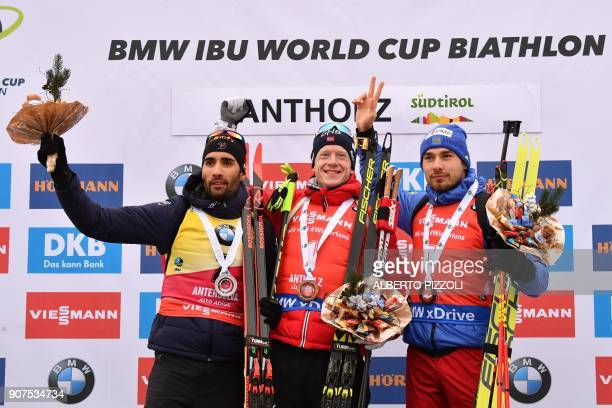 Winner Johannes Thingnes Boe of Norway Martin Fourcade second and Anton Shipulin of Russia third celebrate on the podium of the Men's 125 km Pursuit...