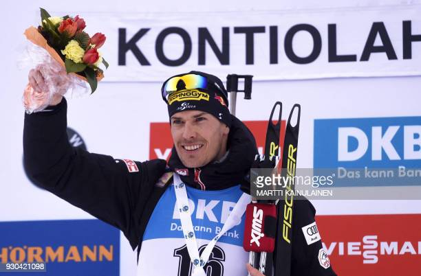 Winner Julian Eberhard of Austria poses on the podium after the men's 15km mass start event at the IBU Biathlon World Cup in Kontiolahti Finland on...