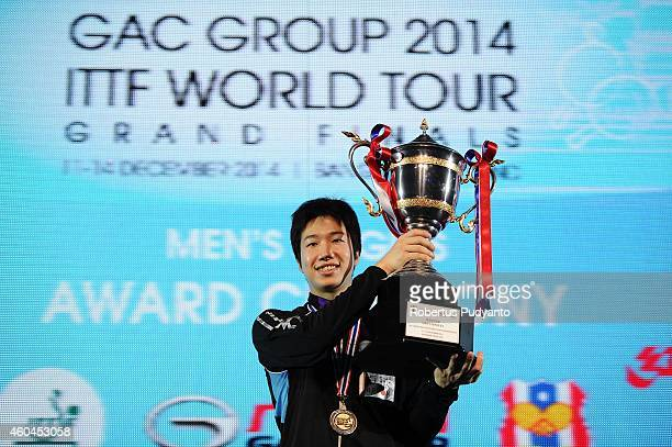 Winner Jun Mizutani of Japan poses with the trophy on the podium during the awarding ceremony of the 2014 ITTF World Tour Grand Finals at Huamark...