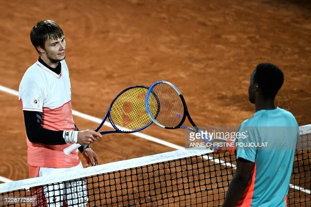 Winner Kazakhstan's Alexander Bublik is congratulated by France's Gael Monfils as they touch their rackets at the end of their men's singles first...