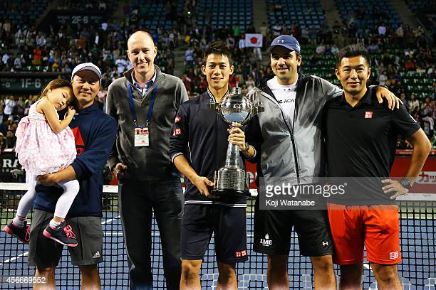 Winner Kei Nishikori of Japan poses with Michael Chang Olivier Van Lindonk Dante Bottini and Koichi Nakao for photographs on the court after winning...