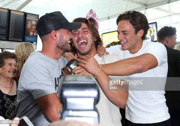 Winner Kem Cetinay of Love Island is mobbed by his mates as he arrive at Stanstead airport after winning Love Island on July 25 2017 in London England