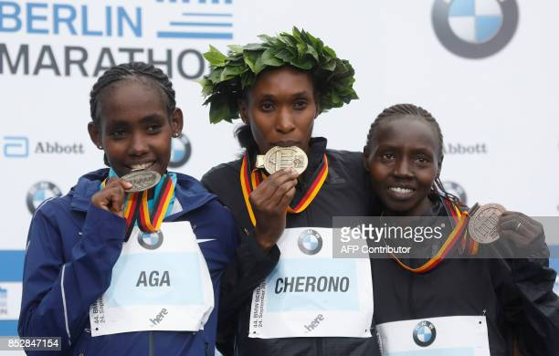 Winner Kenyan Gladys Cherono second placed Ethiopian Ruti Aga and third placed Kenyan Valary Aiyabei celebrate on the podium at the Berlin Marathon...
