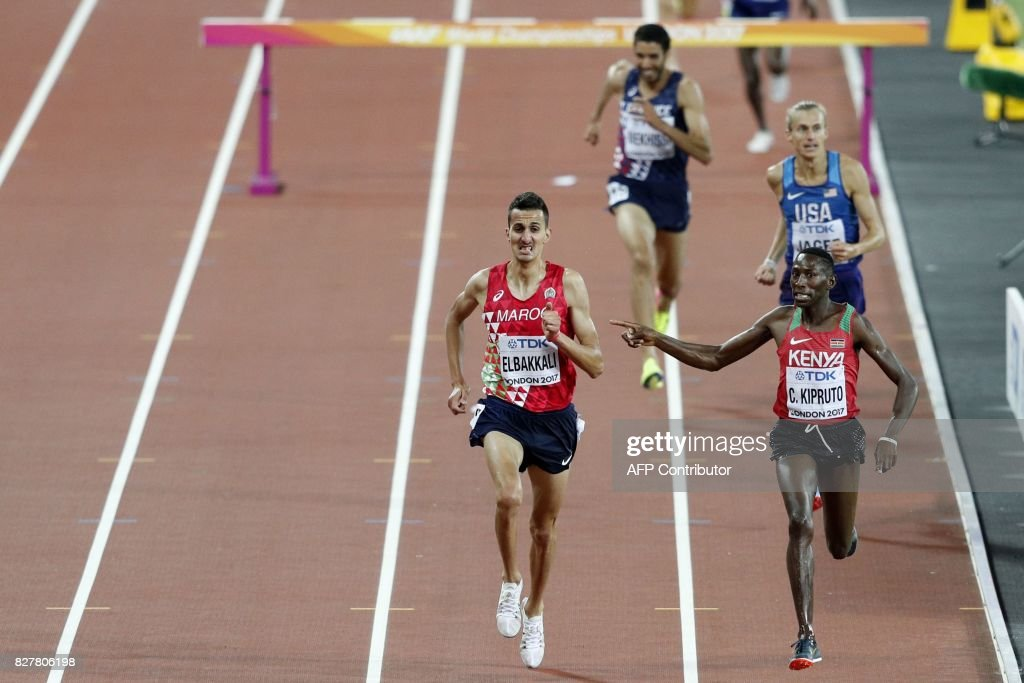 TOPSHOT - Winner, Kenya's Conseslus Kipruto (R) gestures to Morocco's Soufiane Elbakkali as they race to the finish in the final of the men's 3,000m steeplechase athletics event at the 2017 IAAF World Championships at the London Stadium in London on August 8, 2017. / AFP PHOTO / Adrian DENNIS