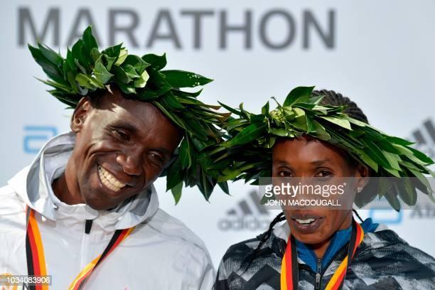 Winner Kenya's Eliud Kipchoge and women's winner Kenya's Gladys Cherono pose after the winner's ceremony after the Berlin Marathon on September 16...