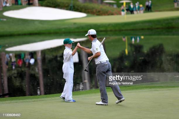 Winner Kevin Streelman and his caddie Ethan Couch bump fists on No 9 during the Par 3 Contest for the Masters at Augusta National on Wednesday April...