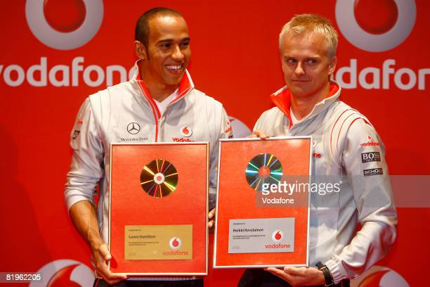 Winner Lewis Hamilton and Heikki Kovalainen of the Vodafone McLaren Mercedes team pose with their commorative discs presented after competing in the...