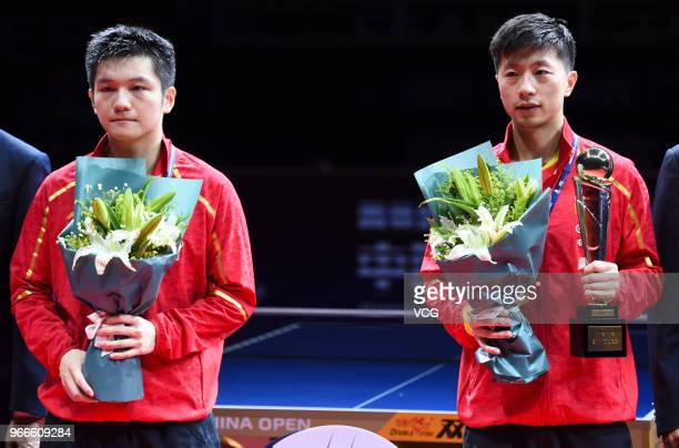 Winner Ma Long of China and runnerup Fan Zhendong of China attend awarding ceremony after men's singles final match on day four of the 2018 ITTF...