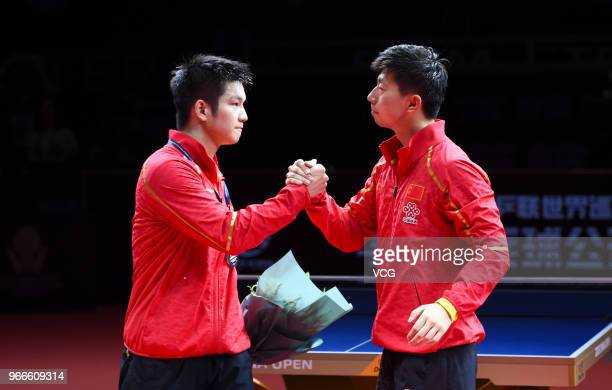 Winner Ma Long of China and runnerup Fan Zhendong of China shake hands after men's singles final match on day four of the 2018 ITTF World Tour China...